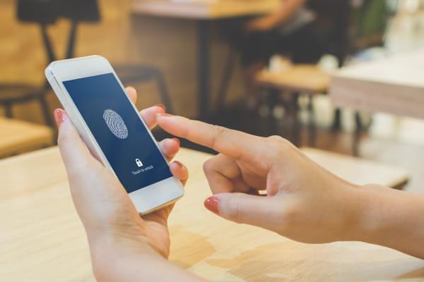 Assinatura digital na SST: usuário desbloqueando celular com digital.
