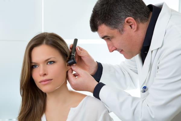 Audiometria ocupacional: médico avaliando a audição de uma funcionária.