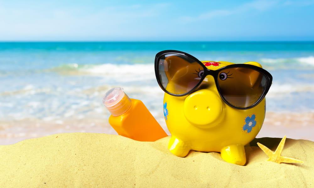 Como funcionam as férias coletivas: porquinho cofrinho na areia da praia.