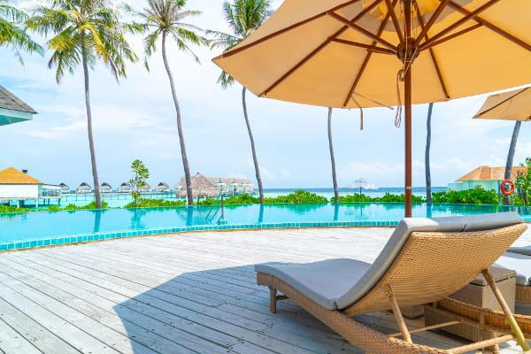 Como funcionam as férias coletivas: cadeira a beira da piscina em frente a praia.