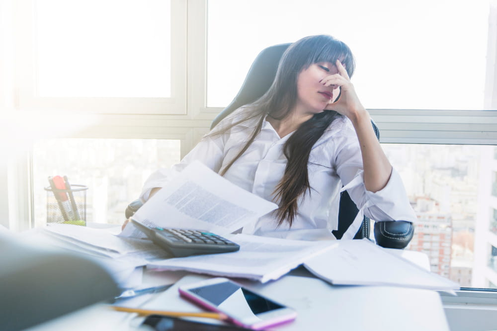Como reduzir o absenteísmo na empresa: mulher angustiada por falta de reconhecimento.