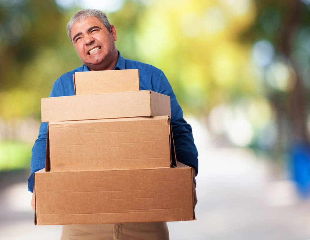 Doenças ocupacionais: como evitá-las: homem carregando peso excessivo.