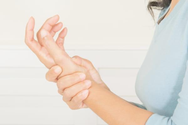 Doenças ocupacionais: como evitá-las: mulher massageando o pulso.