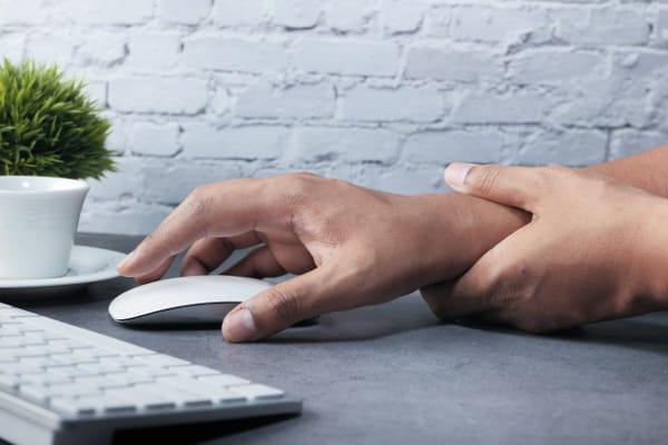 Doenças ocupacionais mais recorrentes: usuário acessando notebook com o mouse.