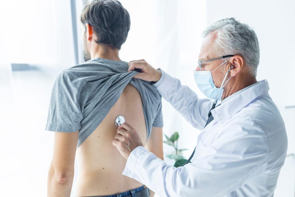 Doenças ocupacionais mais recorrentes: médico ouvindo o pulmão de um paciente.