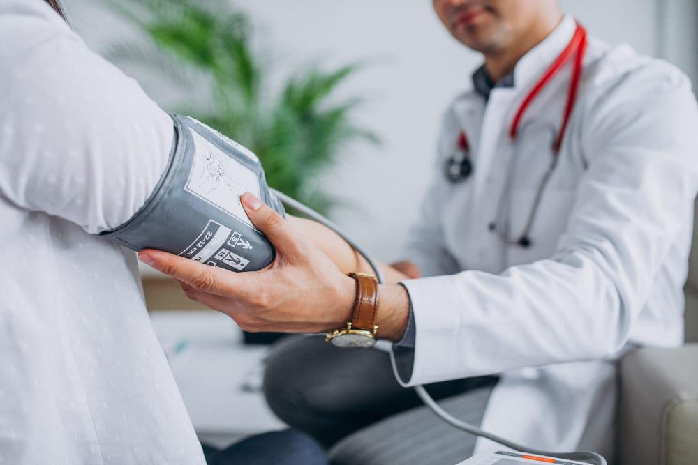 Exame de retorno ao trabalho: médico medindo a pressão de um trabalhador.