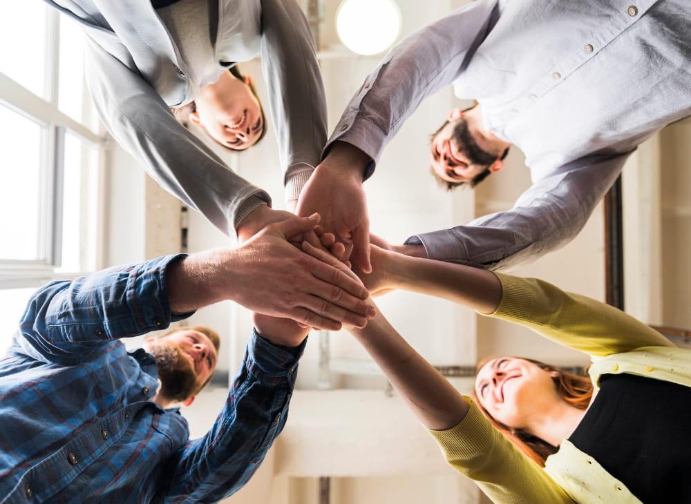 6 motivos para fazer gestão SST na sua empresa: equipe dando as mãos.