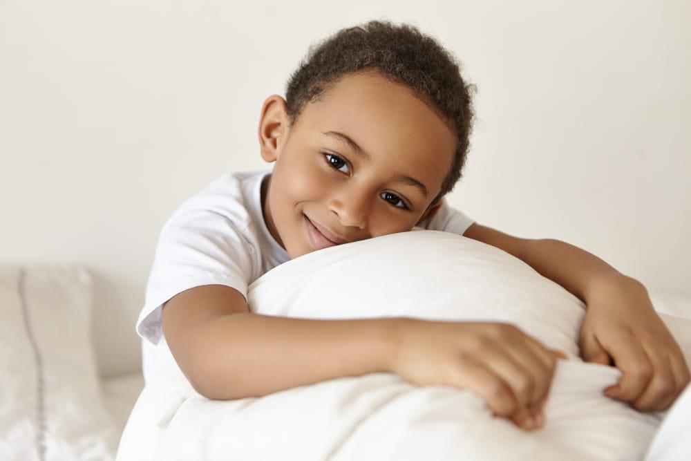 Boas notícias de 2020 para renovar as esperanças: garoto abraçado ao travesseiro.