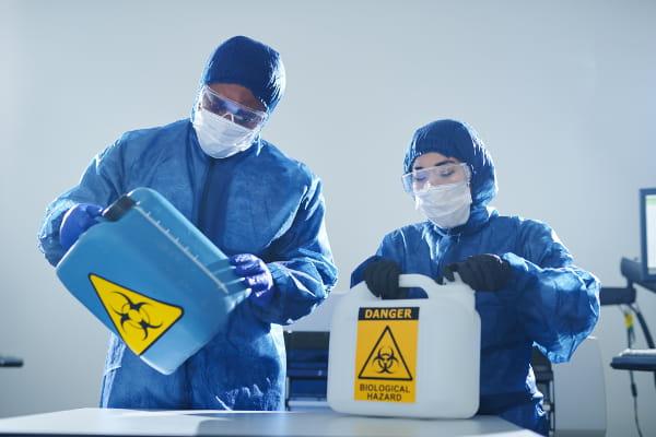 Saiba o que são riscos ambientais: especialistas manuseando produtos químicos.