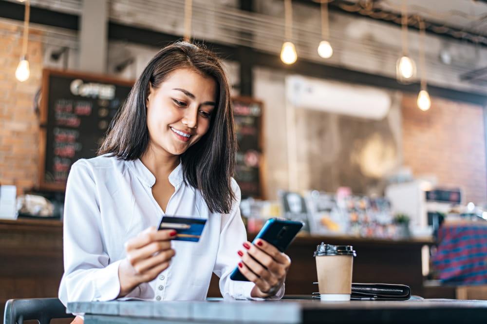 PIX no pagamento da Guia do eSocial: mulher com cartão na mão para pgar contas.