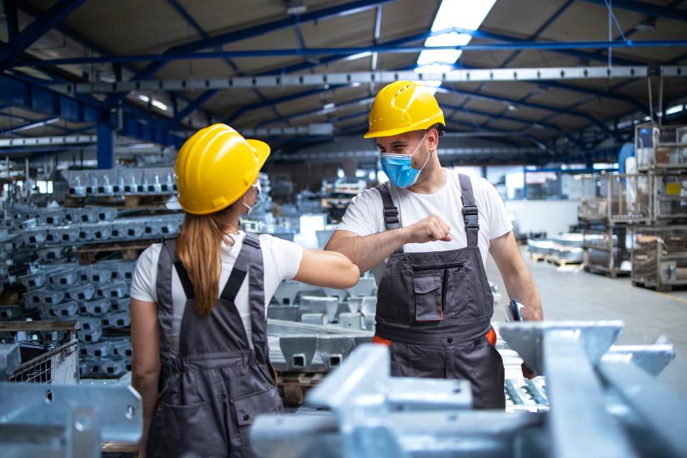 Principais conceitos de Saúde e Segurança do Trabalho: colegas de trabalho se cumprimentando com o cotovelo.