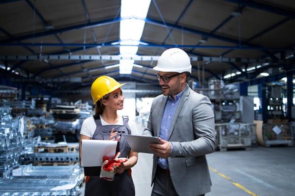 Principais conceitos de Saúde e Segurança do Trabalho: funcionários analisando estratégias na fábrica.