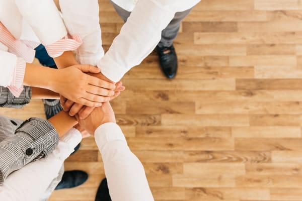 Promoção de saúde no trabalho: equipe apertando suas mãos.