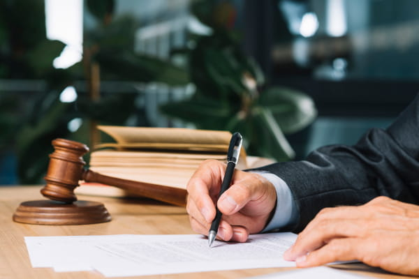 Reforma trabalhista e os principais pontos para a SESMT: pessoa assinando documentos.