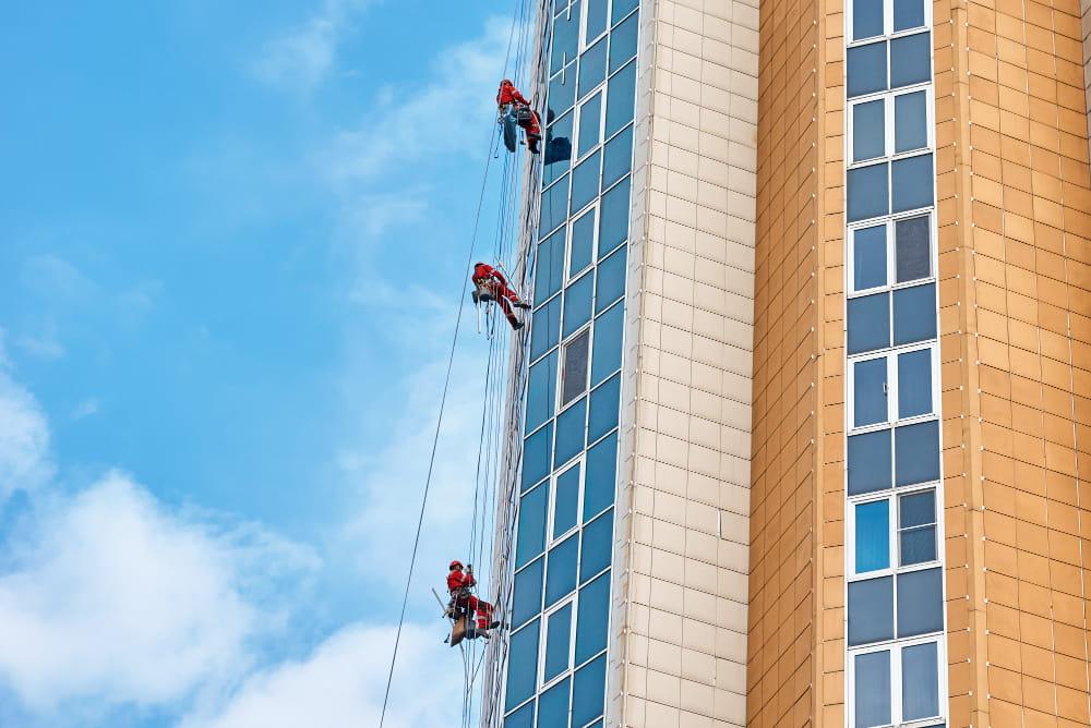 Risco grave e iminente na segurança do trabalho: trabalhadores limpando um edifício pelo lado de fora.